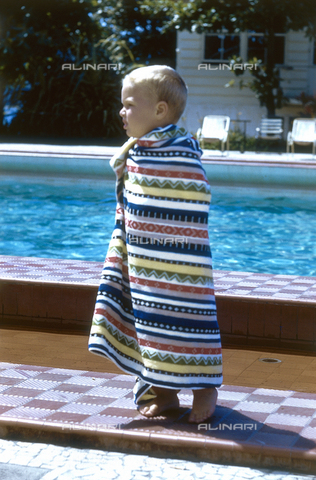 NVQ-S-000520-0060 - Little boy wrapped in a towel on the edge of a pool