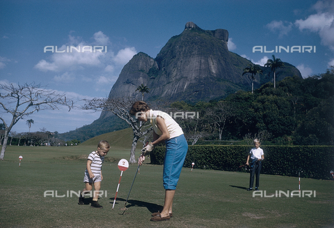 NVQ-S-000520-0064 - Young woman with two children on a putting green; America