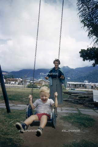 NVQ-S-000520-0089 - Mother pushing her son in a swing; America