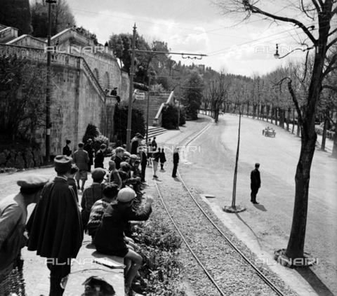 NVQ-S-002202-0012 - Group of people attends a car race on viale Galileo in Florence. On the left the access ramps to the Church of San Miniato al Monte - Date of photography: 1930-1940 ca. - Alinari Archives, Florence