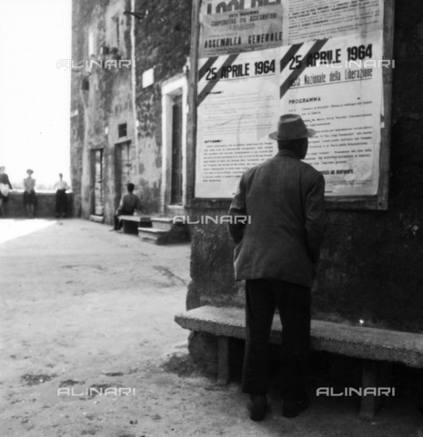OMD-S-000355-0002 - A man reads a poster of the National Day of Liberation of April 25, 1964 - Date of photography: 25/04/1964 - Fratelli Alinari Museum - donation Orioli, Florence