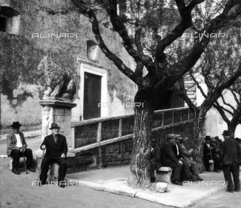 OMD-S-000355-0010 - Elderly people in the square in front of the entrance to the Orsini palace with the stone lion, Pitigliano - Date of photography: 1964 - Fratelli Alinari Museum - donation Orioli, Florence