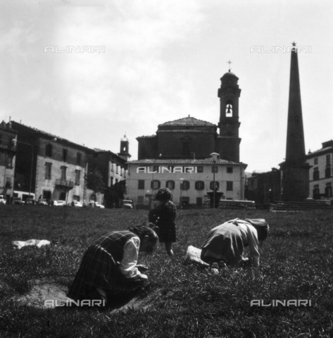 OMD-S-000355-0011 - Girls play in a meadow of Castel del Piano; the background the spire of the Church of the Opera or the Nativity of Mary - Date of photography: 1964 - Fratelli Alinari Museum - donation Orioli, Florence