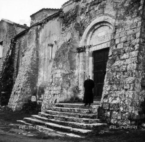 OMD-S-000357-0002 - A priest on the steps of the Cathedral of Saints Peter and Paul in Sovana - Date of photography: 1964 - Fratelli Alinari Museum - donation Orioli, Florence
