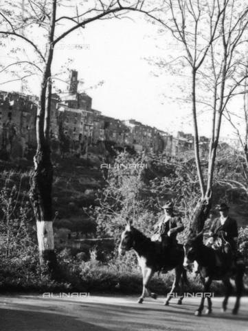 OMD-S-000358-0013 - Two men with donkeys on a street at the base of the village of Pitigliano - Date of photography: 1964 - Fratelli Alinari Museum - donation Orioli, Florence