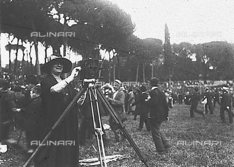 PAS-F-000330-0000 - Ritratto di signora con macchina fotografica montata su treppiede, mentre scatta una fotografia, in occasione del concorso ippico di Piazza di Siena - Data dello scatto: 1921 - Istituto Luce/Gestione Archivi Alinari, Firenze