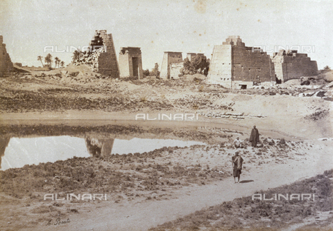 PDC-A-004574-0017 - View of the archaeological site of Karnak in Egypt. In the foreground, the sacred lake behind which are the ruins of ancient buildings, including the Temple of Khonsu - Data dello scatto: 1870-1880 ca. - Archivi Alinari, Firenze