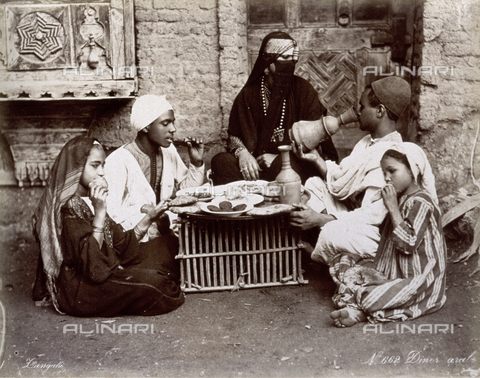 PDC-A-004676-0005 - Arab family shown eating supper. The members of the small group are seated on the ground around a rudimentary table on which is a large tray full of dishes