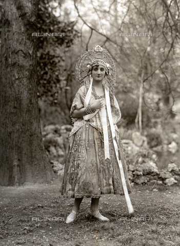 PDC-F-000246-0000 - Portrait of a woman dressed as an odalisque (?) in a garden. She wears a curious hat, decorated with beads, pendants and long ribbons - Date of photography: 1920-1925 ca. - Alinari Archives-Palazzoli Collection, Florence