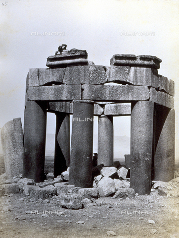 PDC-F-000360-0000 - View of a funerary structure in Baalbek. It is octagonal in plan with eight large smooth columns, with an architrave and parts of the trabeation. At the top, lying down, a local boy. Around are ruins of the roofing - Date of photography: 1865 - 1870 ca. - Alinari Archives-Palazzoli Collection, Florence