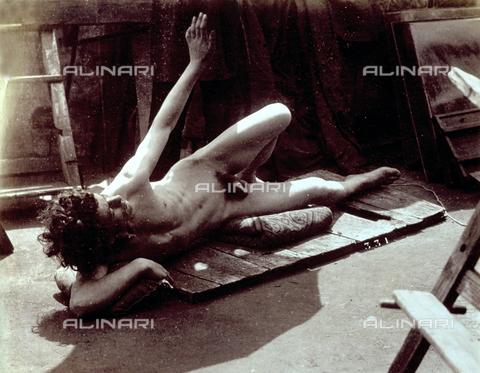 PDC-F-000528-0000 - Un giovane uomo posa nudo, all'interno di uno studio, disteso su una tavola di legno. Il modello è ritratto a figura intera, di profilo con il braccio sinistro sollevato - Data dello scatto: 1890 ca. - Archivi Alinari, Firenze