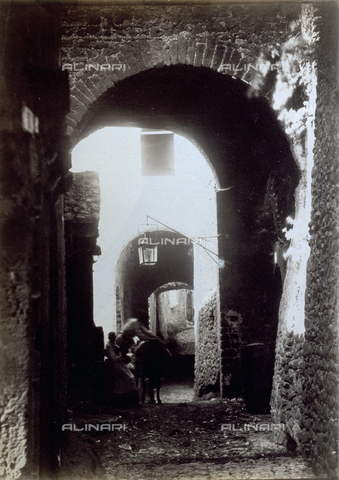 PDC-F-000545-0000 - Passage archways between the houses in a hamlet. In the background, a woman is seated with a horse next to her. In the foreground, a lantern is hung on the inner wall of the archway - Data dello scatto: 1872 - Archivi Alinari, Firenze
