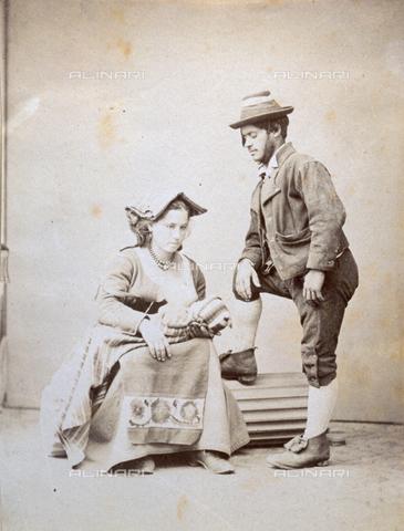 PDC-F-000548-0000 - Ritratto di coppia in abiti tradizionali con neonato. La donna, seduta, tiene sulle ginocchia il piccolo bambino avvolto in una coperta. L'uomo, in piedi, appoggia un piede su di un rocchio di colonna (da studio fotografico) e rivolge lo sguardo verso il bambino - Data dello scatto: 1855 -1865 ca. - Archivi Alinari, Firenze