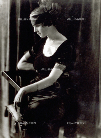 PDC-F-000574-0000 - Ritratto di profilo, di giovane donna in abito da sera degli anni '20, seduta su una sedia, con i capelli raccolti in una fascia - Data dello scatto: 1920 ca - Archivi Alinari-collezione Palazzoli, Firenze
