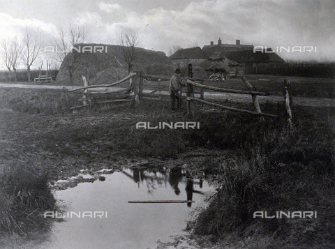 PDC-F-000684-0000 - Country landscape with houses and farm buildings. In the foreground a marsh bordered by a fence at which a farmer is protrayed - Data dello scatto: 1886 ca. - Archivi Alinari, Firenze