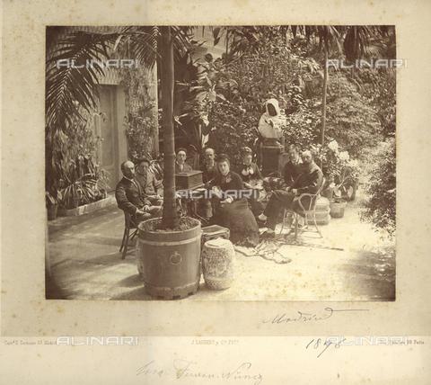 PDC-F-001327-0000 - Ritratto di gruppo con uomini e donne seduti ad un tavolo in un angolo di giardino ricco di piante e vari oggetti - Data dello scatto: 1876 - Archivi Alinari, Firenze