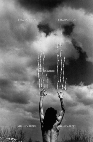 PDC-F-001402-0000 - Experimental photo, showing a man seen from behind, his back bare and his hands raised as if he were trying to scratch the sky. The photographer has intervened to create an unsettling effect of lacerations on the clouds - Date of photography: 1972 - Alinari Archives-Palazzoli Collection, Florence