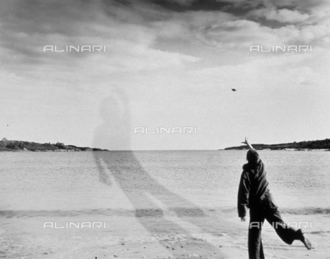 PDC-F-001403-0000 - Artistic photograph of a boy or a girl seen from behind, throwing something into the sea. The shadow on the water appears enormous - Date of photography: 1973 - Alinari Archives-Palazzoli Collection, Florence