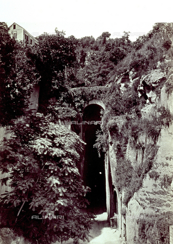 PDC-F-001817-0000 - Exterior of the grotto of Pozzuoli. The grotto opens at the center of a rocky landscape covered in vegetation. Above, to the left, a house can be glimpsed - Data dello scatto: 1860-1880 ca. - Archivi Alinari, Firenze