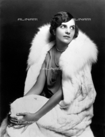 PDC-F-002151-0000 - Ritratto di giovane donna seduta, le mani intorno al ginocchio; è vestita elegantemente, con abito da sera e pelliccia, stile Anni Venti - Data dello scatto: 1925-1930 ca. - Archivi Alinari, Firenze