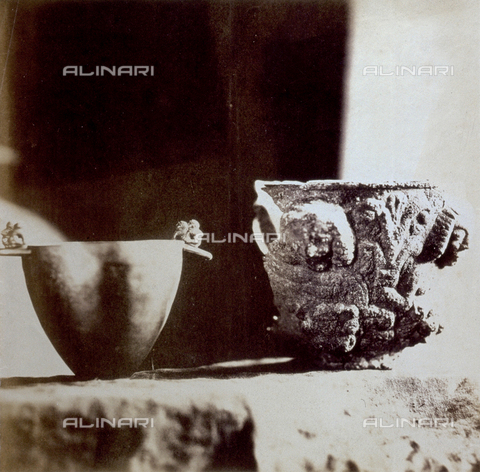 PDC-F-002396-0000 - Due raffinate opere d'arte tunisine: un vaso in metallo dalla superficie liscia e lucente, coi soli manici decorati, è posto a paragone con un capitello romanico interamente ricoperto di ornamenti a rilievo antropomorfi e fitomorfi - Data dello scatto: 1870-1880 ca. - Archivi Alinari, Firenze