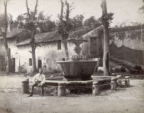 PDC-F-003212-0000 - A small piazza in the Trastevere district of Rome. In the foreground a fountain with a man sitting on the guard rail. In the background a modest house which is a bit dilapidated - Data dello scatto: 1870 ca. - Archivi Alinari, Firenze