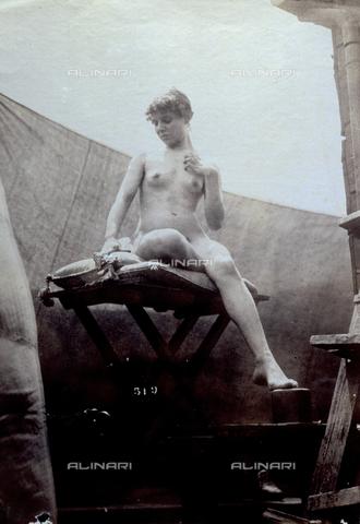 PDC-F-004167-0000 - Ritratto di giovane donna nuda. La modella posa, in atteggiamento statuario, seduta su di un tavolino ricoperto di cuscini, con il volto lievemente reclinato verso il petto e con la mano sinistra sopra il seno. Una tenda fa da sfondo - Data dello scatto: 1890 ca. - Archivi Alinari, Firenze