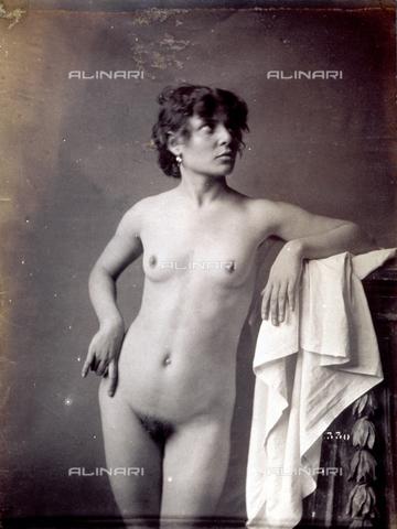 PDC-F-004168-0000 - Giovane modella ritratta, nuda, in studio. La donna posa con il braccio sinistro appoggiato ad un piedistallo coperto da un drappo leggero ed il viso rivolto lateralmente - Data dello scatto: 1890 - 1900 ca. - Archivi Alinari, Firenze