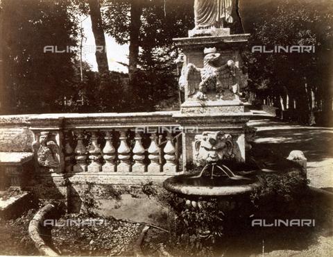 PDC-S-000461-0002 - L'immagine riproduce in primo piano una balaustra marmorea terminante in una piccola fontana in cui l'acqua sgorga da un mascherone applicato al basamento di una statua. Tale basamento è ulteriormente decorato da un'aquila ad altorilievo. A destra e sullo sfondo un viale alberato e fitta vegetazione - Data dello scatto: 1870-1890 ca. - Archivi Alinari, Firenze