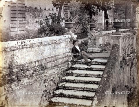 PDC-S-000461-0011 - Un uomo dorme seduto su una scalinata. Alle sue spalle si intravedono alberi e le pareti di un edificio - Data dello scatto: 1870-1890 ca. - Archivi Alinari, Firenze