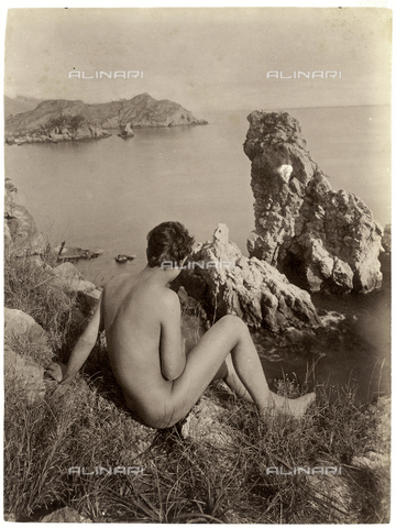 PDC-S-000865-0003 - Portrait from the rear of a nude adolescent. He is sitting on some small rocks in front of the sea - Data dello scatto: 1914 ca. - Archivi Alinari, Firenze