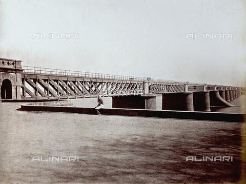 PDC-S-001878-0005 - Ponte in struttura metallica. Sulla spalletta dell'argine, in primo piano, è seduto un indiano in costume etnico - Data dello scatto: 1870 -1880 ca. - Archivi Alinari, Firenze