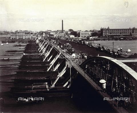 PDC-S-003980-0007 - Veduta del ponte sul fiume Hugli a Calcutta, in India. La scena è animata dal passaggio di persone e di mezzi di locomozione. Sullo sfondo, una ciminiera - Data dello scatto: 1880-1890 - Archivi Alinari, Firenze
