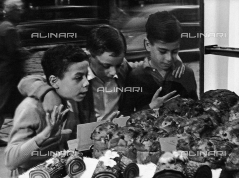 PTA-F-000217-0000 - Three little boys admire the display window of a bakery showing panettoni and cakes, Milan