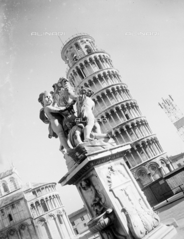 PTA-S-001302-0005 - Fountain with the marble group of putti holding the coats of arms of Pisa and the Opera; in the background the leaning tower, Pisa - Data dello scatto: 1930-1940 - Archivi Alinari, Firenze