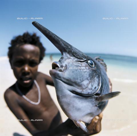 QFA-F-000054-0000 - Un bambino somalo mostra un pesce Naso brevirostris finito nelle reti davanti alla Costa di Merka in Somalia - Data dello scatto: 1967 - Folco Quilici © Fratelli Alinari