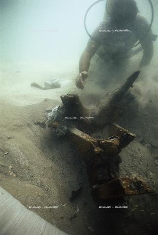 QFA-S-000954-000P - In un basso fondale nelle acque di Haifa, il dritto di prua di un relitto fenicio del VII sec. a. C., mentre un archeosub del museo di haifa ne inizia il recupero. Israele - Data dello scatto: 1987 - Folco Quilici © Fratelli Alinari