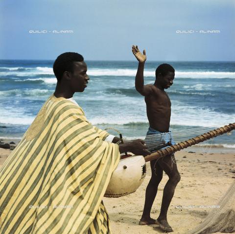 QFA-S-003758-00FQ - Un griot, un cantastorie e il suo strumento accompagnano il canto di un pescatore. Isola di Gorée. Senegal - Data dello scatto: 1966 - Folco Quilici © Fratelli Alinari