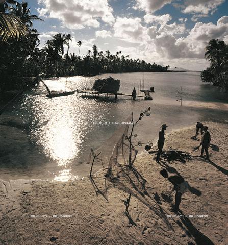 """QFA-S-009608-00SP - """"Magic hour"""" sulla laguna di un motù, piccola isola all'interno dei maggiori atolli polinesiani: un gruppo di raccoglitori di """"nacres"""" (ostrica madreperlacea, avolte perlifera) accampato per l'annuale stagione di raccolta. Arcipelago delle Tuamutu - Data dello scatto: 1961 - Folco Quilici © Fratelli Alinari"""