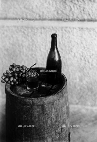 RCB-F-004975-0000 - Tino con bottiglia, un bicchiere di vino e un grappolo d'uva - Archivio Bruni/Gestione Archivi Alinari, Firenze