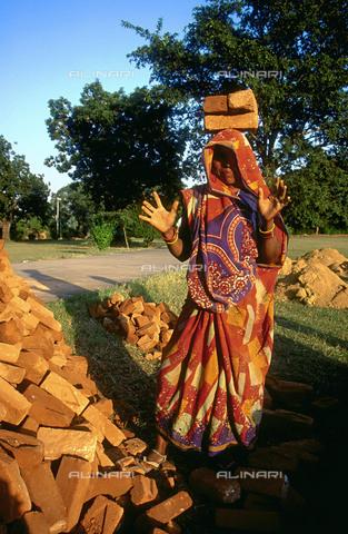 RCS-S-CP0048-4724 - Donna muratore che porta mattoni sulla testa a Khajuraho nel Madhya Pradesh in India - Data dello scatto: 1990-1999 - RCS / Gestione Archivi Alinari, Firenze