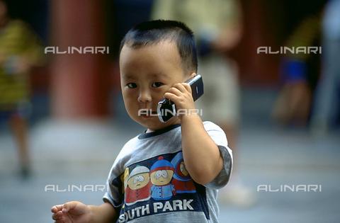 RCS-S-CP0057-5688 - Ritratto di un bambino con il telefono cellulare. Pechino, in Cina - Data dello scatto: 1990-1999 - RCS / Gestione Archivi Alinari, Firenze