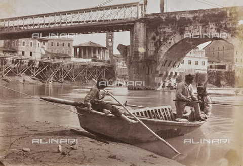 REA-F-000358-0000 - Boating on the river under the bridge Emilio (today Ponte Rotto) in Rome connected to the left bank of the Tiber with a metal walkway supported by ropes. In the background the Temple of Hercules Victor (called temple of Vesta), down scaffolding for the construction of the embankments and the fornix of the Cloaca Maxima - Data dello scatto: 1880-1884 ca. - Archivi Alinari, Firenze