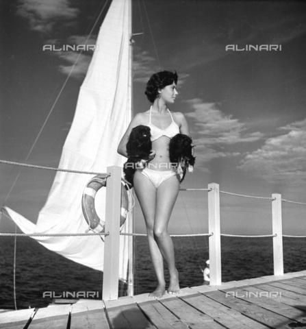 RVA-S-005719-0014 - Una modella che posa in bikini insieme a due cani. Spiaggia di Deauville, agosto 1950. LIP-79390 - Data dello scatto: 1950 - Studio Lipnitzki / Roger-Viollet/Alinari