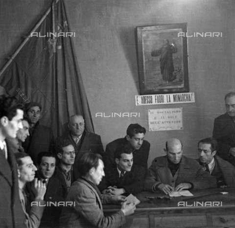 """RVA-S-008445-0002 - Cellula comunista durante la campagna elettorale del 1946 per la proclamazione dell'Assemblea Costituente e il referendum per l'abolizione della monarchia. Sul muro, la scritta: """"E adesso fuori la Monarchia"""" - Data dello scatto: 1946 - Roger Berson / Roger-Viollet/Alinari"""