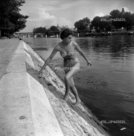 RVA-S-009119-0003 - Giovane ragazza in bikini sugli argini della Senna. Parigi, luglio 1955. RV-112359 - Data dello scatto: 1955 - Roger-Viollet/Alinari