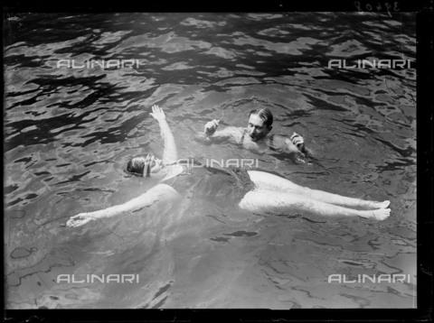 """RVA-S-190668-0019 - Lezione di nuoto nella piscina galleggiante Deligny vicino alla Senna lungo il Quai Anatole-France di Parigi (VII arrondissement). Fotografia proveniente dalla raccolta della rivista """"Excelsior"""" - Data dello scatto: 13/07/1920 - Roger-Viollet/Alinari, Excelsior – L'Equipe"""