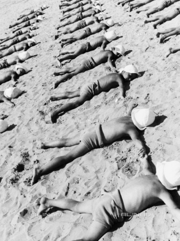 TCI-S-000288-AR09 - Bambini di una colonia sdraiati sulla spiaggia per i bagni di sole - Data dello scatto: 1930 ca. - Touring Club Italiano/Gestione Archivi Alinari