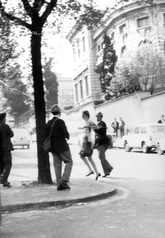 TEA-F-000016-0000 - Studentessa accompagnata da un poliziotto durante le proteste del 1968 presso la Facoltà di Architettura a Valle Giulia - Data dello scatto: 1968 - Archivi Alinari, Firenze