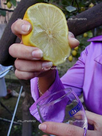 TEA-F-003881-0000 - Primo piano di mani di una donna che spreme un bergamotto in un bicchiere - Data dello scatto: 2000 ca. - Archivi Alinari, Firenze